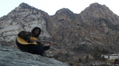 Teenage Girl Sits Outdoors And Strums Her Guitar, By Beautiful Mountains Stock Footage