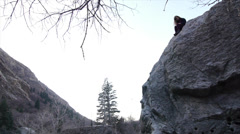 Teen Girl Sitting High On A Big Rock Viewed From A Distance Stock Footage