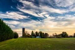 wispy clouds over a water tower and field in shrewsbury, pennsylvania. - stock photo