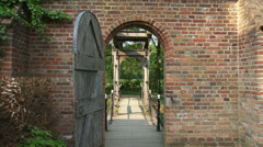View from castle courtyard through gate at drawbridge and moat + pan castle wall Stock Footage