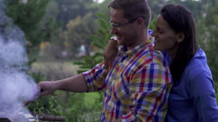 Smiling couple grilling on an outdoor barbecue, slow motion shot at 120fps Stock Footage