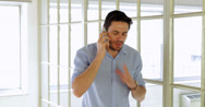 Stock Video Footage of Annoyed young man having a phone call