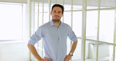 Content handsome man posing with hands on hips - stock footage