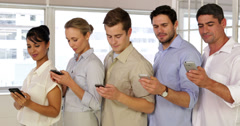 Stock Video Footage of Content businesspeople text messaging while standing in a row