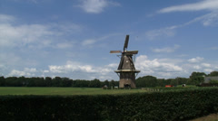 Dutch Windmill gristmill, turning wicks in rural landscape - wide shot Stock Footage