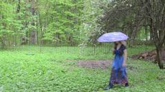 Woman blue umbrella dress tree white bloom petals fall garden Stock Footage