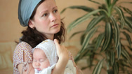 Stock Video Footage of mother with baby in  arms at ceremony of baptism
