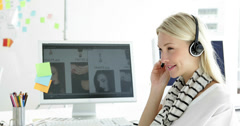 Cute blonde creative designer phoning with headset Stock Footage