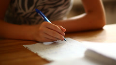 Girl learning math at home, hands holding a pen close-up, with soft focus Stock Footage