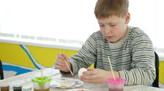 Little boy decorating easter eggs Stock Footage