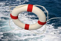 life preserver falling on turbulent water - stock photo