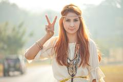 Hippie girl with peace signs Stock Photos
