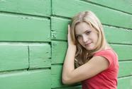 Stock Photo of Austria, Salzkammergut, Mondsee, portrait of young woman leaning at a green