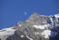 Switzerland, Bernese Oberland, Moon over Klein Fiescherhorn mountain Stock Photos