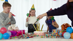 Lighting candles on the cake at kids birthday party Stock Footage