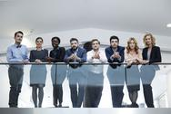 Stock Photo of Germany, Neuss, Group of business people standing behind railing