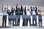 Stock Photo of Germany, Neuss, Group of business people standing behind railing, raising arms