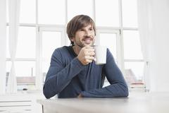 Germany, Munich, Man sitting at table drinking coffee - stock photo