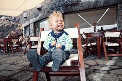 Spain, Lanzarote, laughing little boy sitting on a terrace of a restaurant - stock photo
