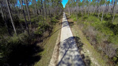 Flying over an empty dirt road through trees Stock Footage