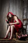 Young woman sitting in a shack dressed as Red Riding Hood, studio shot - stock photo