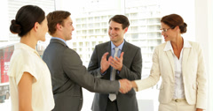 Business people shaking hands at interview while others applaud Stock Footage