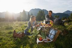 Stock Photo of Austria, Salzburg State, Altenmarkt-Zauchensee, couple having a picnic on alpine
