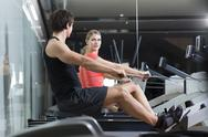 Stock Photo of Austria, Klagenfurt, Man and woman exercising with rowing machine