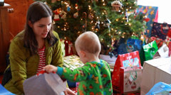 A family opening presents on christmas morning Stock Footage