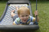 Stock Photo of Little boy lying on a swing in the garden