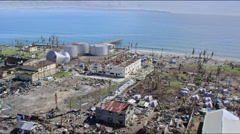 Aerial of huge oil facility with tanks blow away on the coast Stock Footage