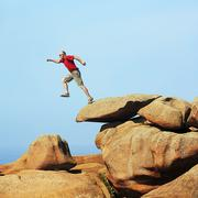 France, Bretagne, Tregastel, Man jumping on rocks Stock Photos