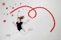 Girl doing rhythmic gymnastics with balls and ribbon Stock Photos