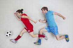 Man and woman running after football - stock photo