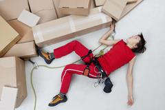 Boy climbing mountains made of cardboard boxes Stock Photos
