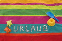 The word Urlaub formed by shells lying between sand toys on a multicolored bath - stock photo