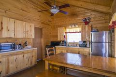 USA, Texas, rustic log home cabin interior with kitchen and dining area Stock Photos