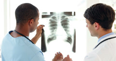 Surgeon and doctor looking over xray together Stock Footage