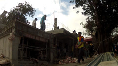Construction Laborers carry long wooden trusses at construction site - stock footage
