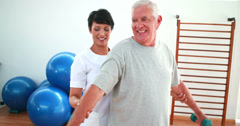 Happy physiotherapist helping elderly patient lift hand weights Stock Footage