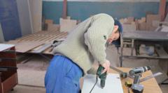 Carpenter using screwdriver assembling furniture Stock Footage