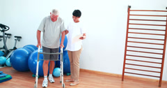 Smiling physiotherapist helping patient walk with walking frame Stock Footage