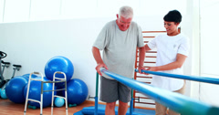 Stock Video Footage of Smiling physiotherapist helping patient walk with parallel bars