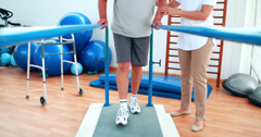 Stock Video Footage of Physiotherapist helping patient walk with parallel bars