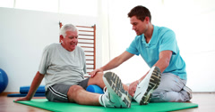 Physiotherapist helping patient with his knee mobility Stock Footage