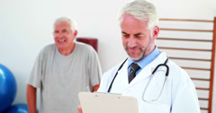 Smiling doctor reading from clipboard Stock Footage
