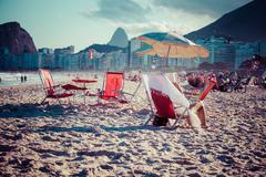 beach chairs and umbrella on beach in rio de janeiro - stock photo