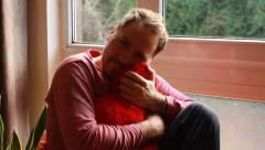 Romantic guy snuggle up heart-shaped cushion Stock Footage