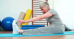 Elderly woman touching her toes on exercise mat Stock Footage