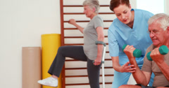 Senior citizens exercising with physiotherapist Stock Footage